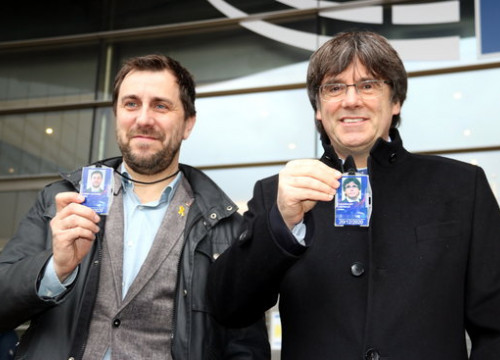 Former Catalan cabinet members Toni Comín and Carles Puigdemont hold up their MEP accreditations on December 20, 2019 (by Nazaret Romero)
